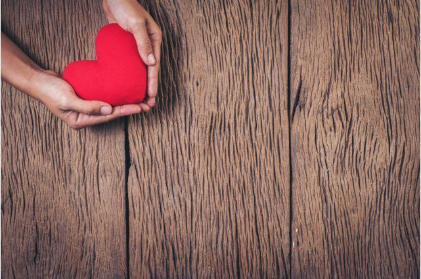 قلبی-قرمز-بین-دو-دست-قرار-گرفته