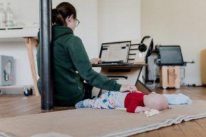 مادری-که-حین-دورکاری-از-نوزادش-مراقبت-میکند